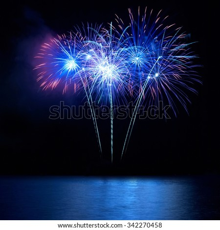 Blue fireworks above water with reflection on the black sky background - stock photo