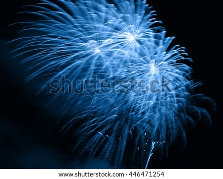 Blue fireworks in the night sky - stock photo