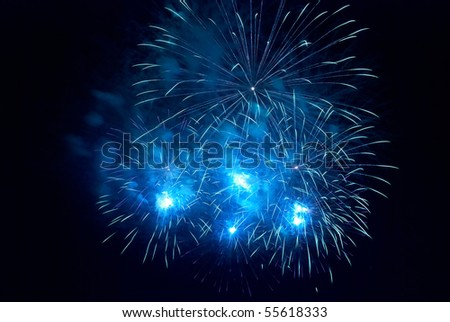 Blue fireworks on the black sky background - stock photo