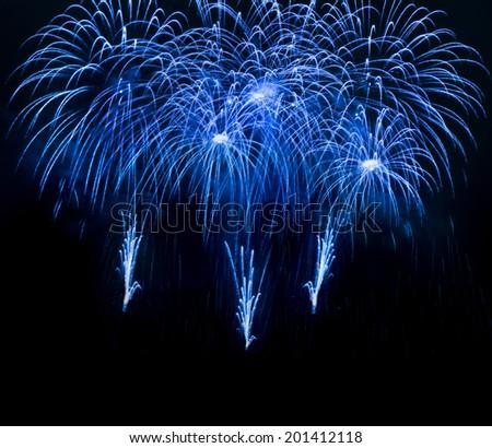 Blue fireworks over night sky background - stock photo