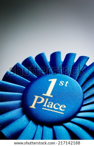 Blue first place winner rosette or badge from pleated ribbon with central text to be awarded to the winner of a competition on a graduated grey background with copyspace - stock photo