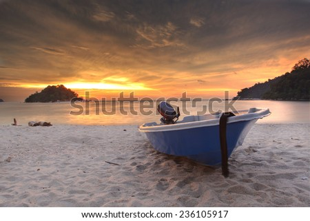 Blue fishing boat at sunset on the beach in Malaysia