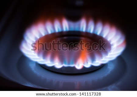 Blue flame gas stove in the dark. - stock photo