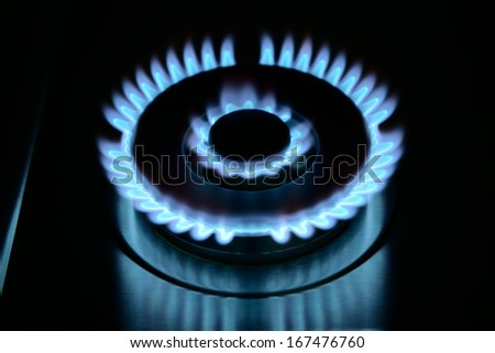 blue flame of gas stove in the dark - stock photo