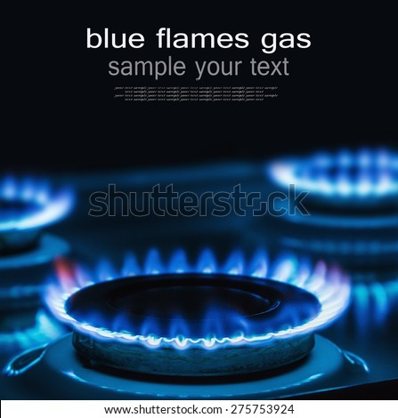Blue flames of gas burning from a kitchen gas stove with space for text on top. Focus the front edge of the hotplate - stock photo