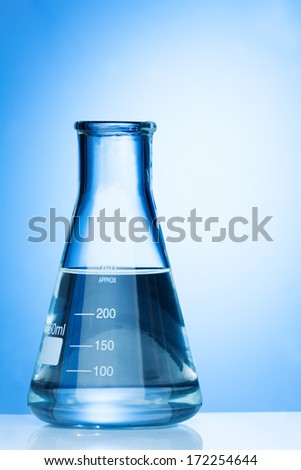 Blue flask in laboratory environment standing on the table with liquid  - stock photo
