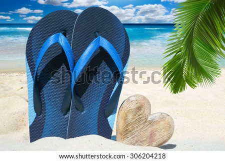 Blue flip flops and a wooden heart with copy space under palm frond on the beach