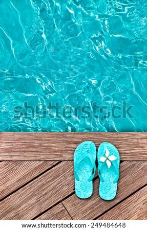 Blue flip flops on a wooden deck - stock photo