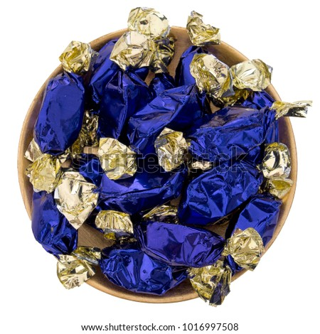 Blue foil wrapped sweets, toffees. On gold colour plate isolated on white.