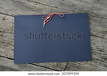 Blue folder on a wooden background with a red and white string tied bow. - stock photo