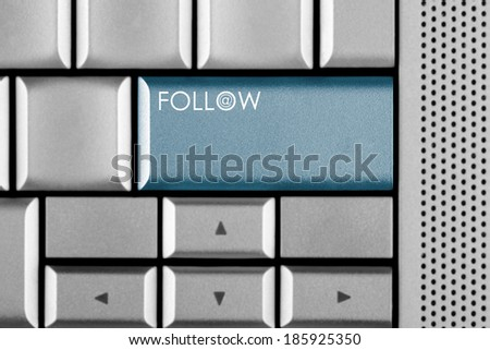 Blue Follow Us key on a computer keyboard with clipping path around the Follow Us key - stock photo