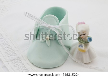 Blue fondant baby booty next to little lady porcelain figurine isolated on white lace - stock photo