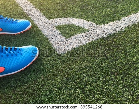 Blue football boots. Blue soccer boots on soccer field.