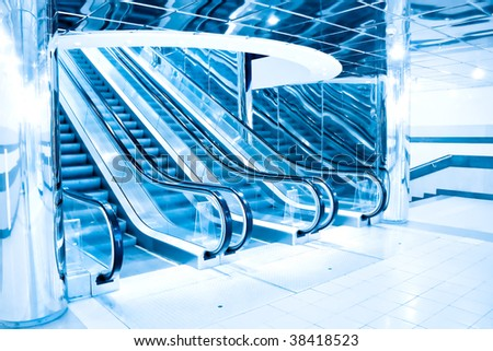 blue footsteps of moving escalator in office center - stock photo