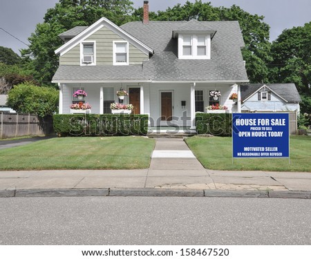 Blue For Sale Real Estate Sign on Front yard Lawn of Suburban Cape Cod Style Home Residential Neighborhood USA - stock photo