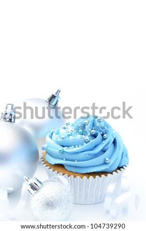 Blue frosty coloured cupcake with festive christmas baubles and ribbons - stock photo
