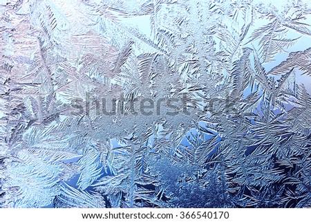 blue frozen window glass with frosty pattern  - stock photo