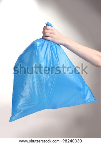blue garbage bag with trash in hand isolated on white - stock photo