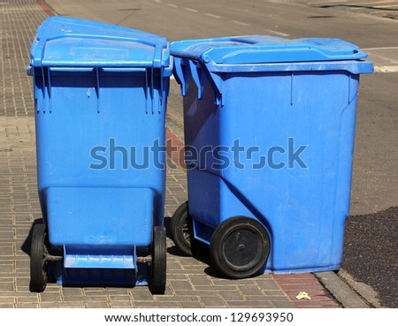 Blue garbage cans on  the sidewalk - stock photo