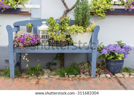 Blue garden bench in front of the house with flowers and decoration / blue garden bench / flowers