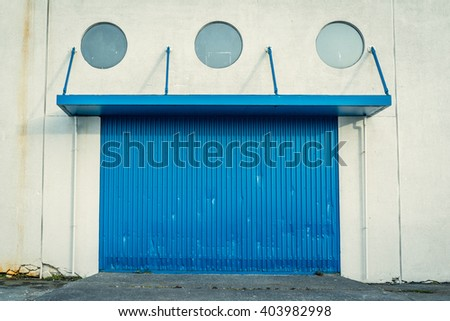 Blue gate on a grungy wall with round windows - stock photo