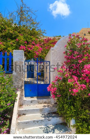 Blue gate to Greek old house decorated with bougainvillea flowers, Firostefani village, Santorini island, Greece