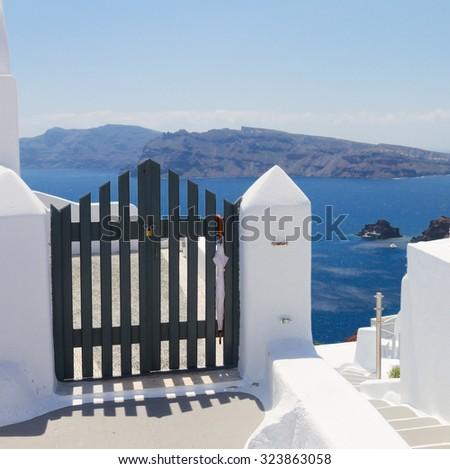 blue gates against volcano caldera and Aegan sea, beautiful details of Santorini island, Greece - stock photo