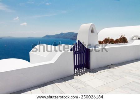 blue gates against volcano caldera and sea, beautiful details of Santorini island, Greece - stock photo