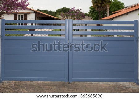 Blue Gates. New family house with blue automatic gates  - stock photo