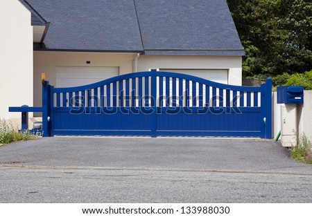 Blue Gates. New family house with blue automatic gates in front of garage door. Picture is taken in Brittany , France and blue color is traditional. Automatic gate, also cantilever gate. - stock photo