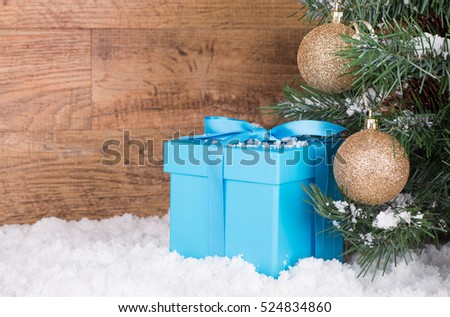 Blue gift box by a Christmas tree with a wood background