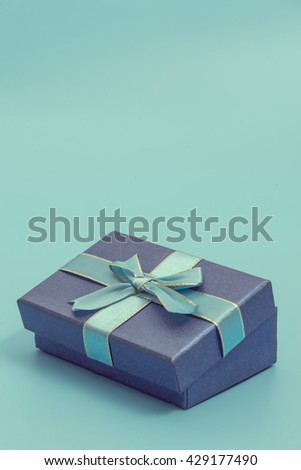 Blue gift box on blue colour background, copyspace for text - stock photo