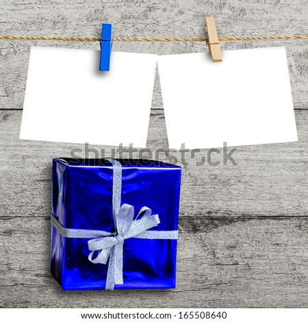 blue gift box on wooden wall with a blank paper hanged  - stock photo