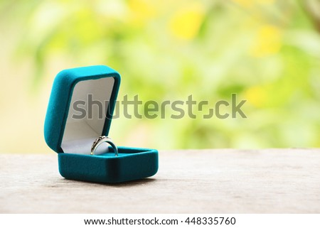 Blue gift box with ring on background of greenery and flowers.Selective focus, toned image, film effect, macro, close-up - stock photo