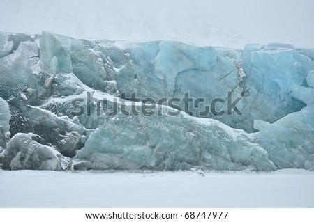 Blue glacier in cold snowy winter day, Greenland