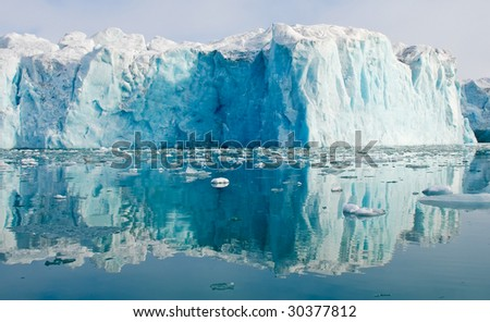 Blue glacier reflecting in the waters of fjord