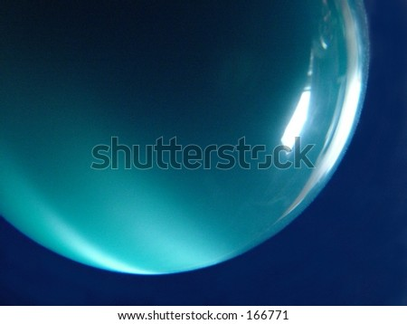 Blue glass ball against dark blue background - stock photo