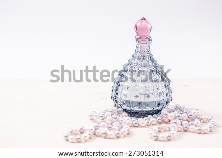 Blue glass bottle of female perfume and Pearl beads. Soft toning. - stock photo