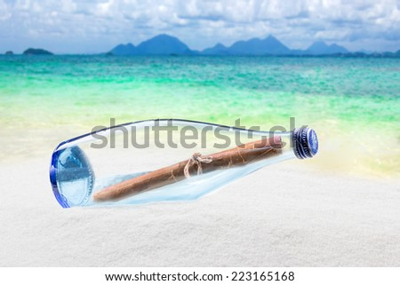 Blue glass bottle on sand and tropical sea - stock photo