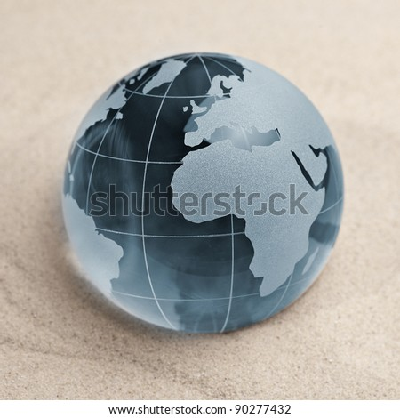 Blue Glass globe on sand background - stock photo