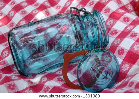 Blue glass jar with a wire holding the lid and rubber ring  onto it, used for canning fruits and vegetables, sitting on  a vintage table cloth. - stock photo