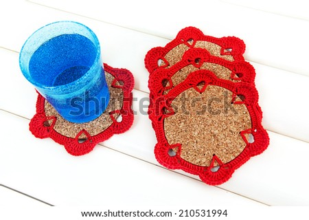 Blue glass on crochet red coaster with cork base - stock photo