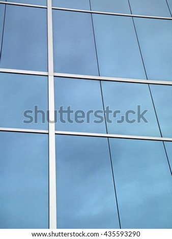 Blue Glass Windows reflect clouds with white lines framing windows. - stock photo