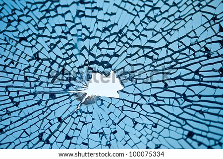 blue glass with many cracks and hole in middle - stock photo