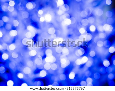 Blue glitter Christmas festive abstract background with bokeh de-focused lights and stars