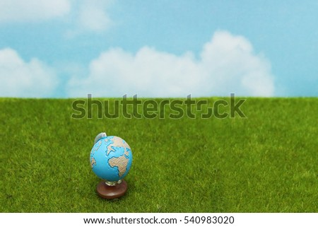 Blue globe on green grass over  blue sky background. World Conservation concept.