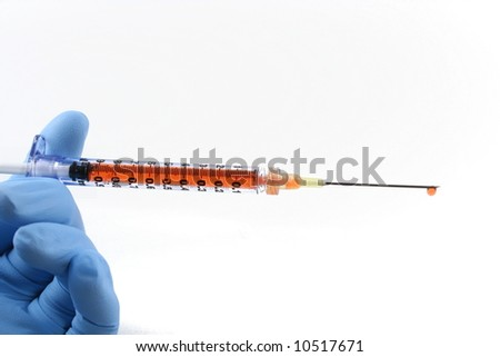blue gloved hand with red liquid filled syringe and needle - stock photo