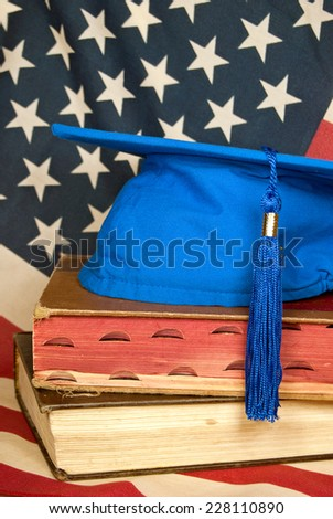 blue graduation cap on old books with American flag background - stock photo