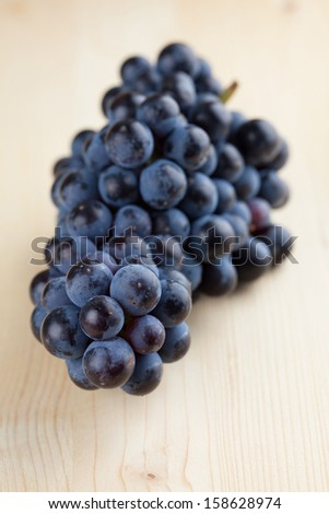 Blue grape cluster on wooden background. Shallow dof