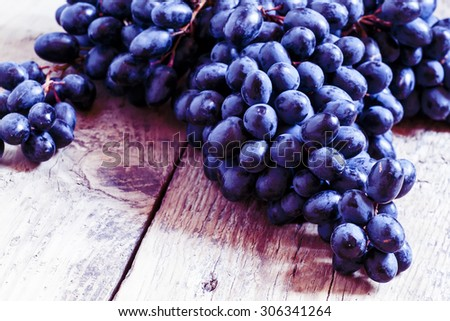 Blue grapes on old wooden background, toned image, selective focus - stock photo